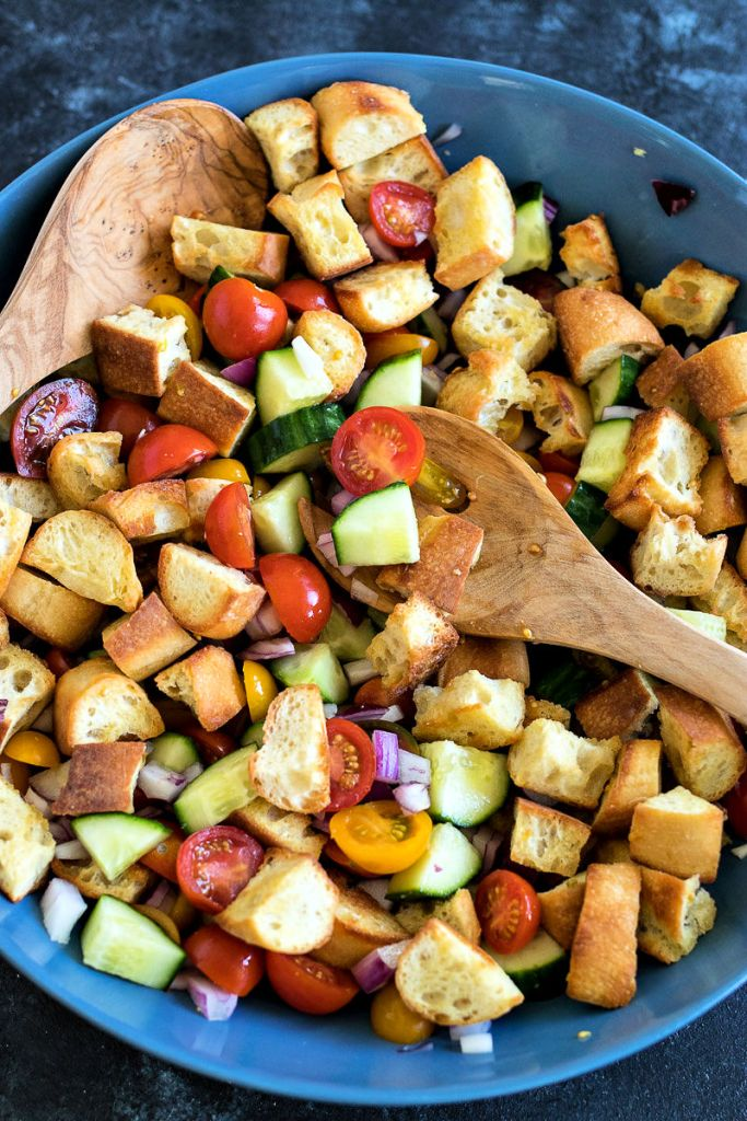Two wooden serving utensils in a bowl of Tomato Panzanella Salad
