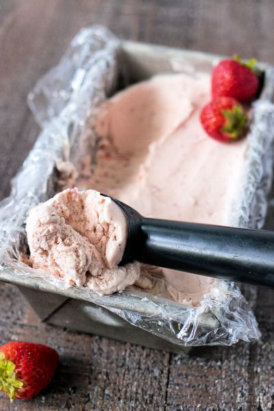 metal loaf pan filled with strawberry balsamic ice cream with an ice cream scoop containing a scoop of ice cream, shot from a side angle