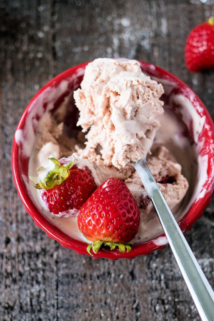 Spoonful of Strawberry Balsamic Ice Cream over a bowl with the ice cream and whole strawberries