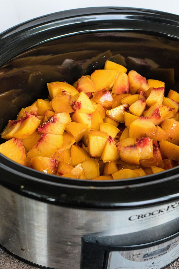 Slow cooker full of peach chunks, sugar and spices