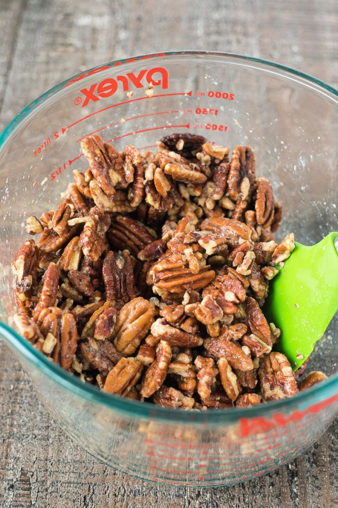 a bowl of raw pecan halves in a large mixing bowl with a green silicone spatula