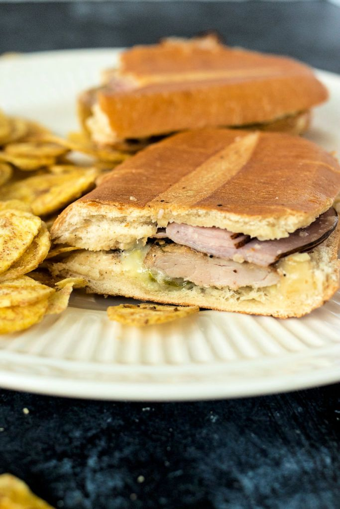 zoomed shot of half of a Cuban sandwich, showing the cut half with all the ingredients exposed sitting on a plate with plantain chips