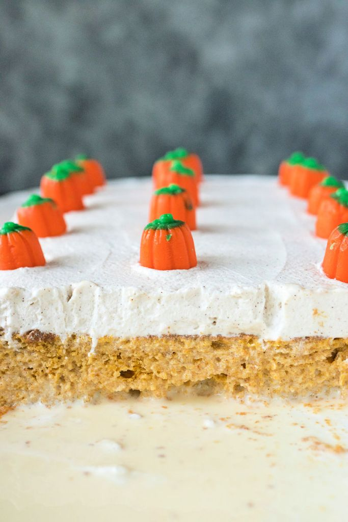 Pan of Pumpkin Tres Leches with pieces cut to show the layer of cake and the layer of cream