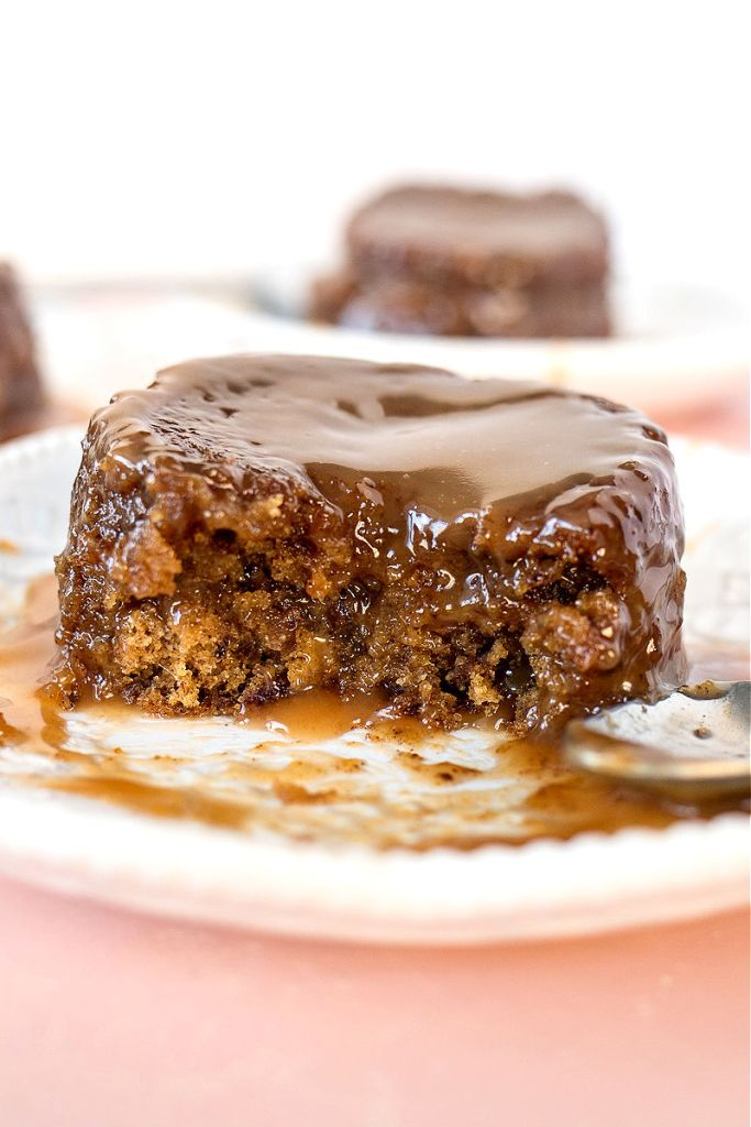 zoomed in shot of sticky toffee pudding on a plate with a few bites removed