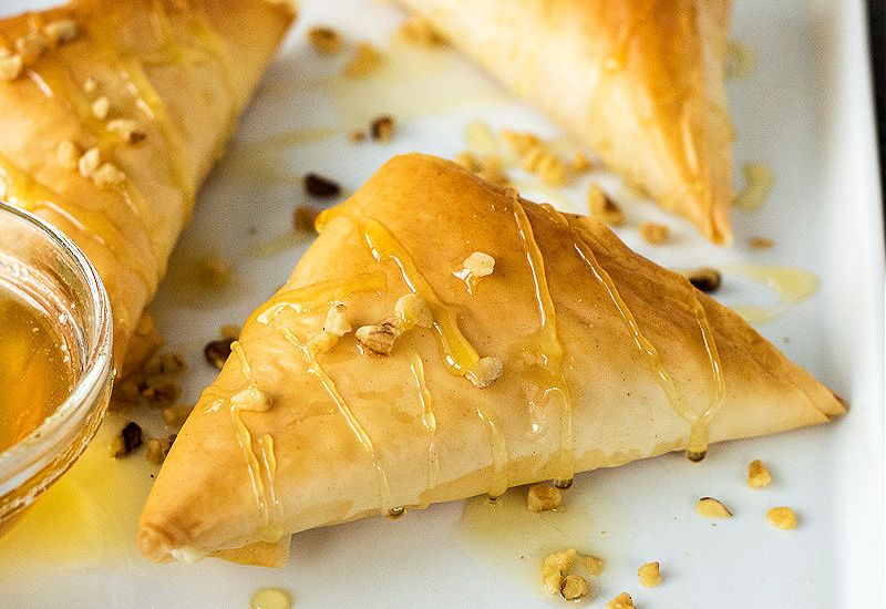 close up of a phyllo triangle sitting on a platter drizzled with honey and chopped walnuts