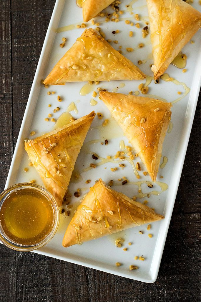 overhead shot of goat cheese phyllo triangles on a platter with drizzles of honey chopped walnuts