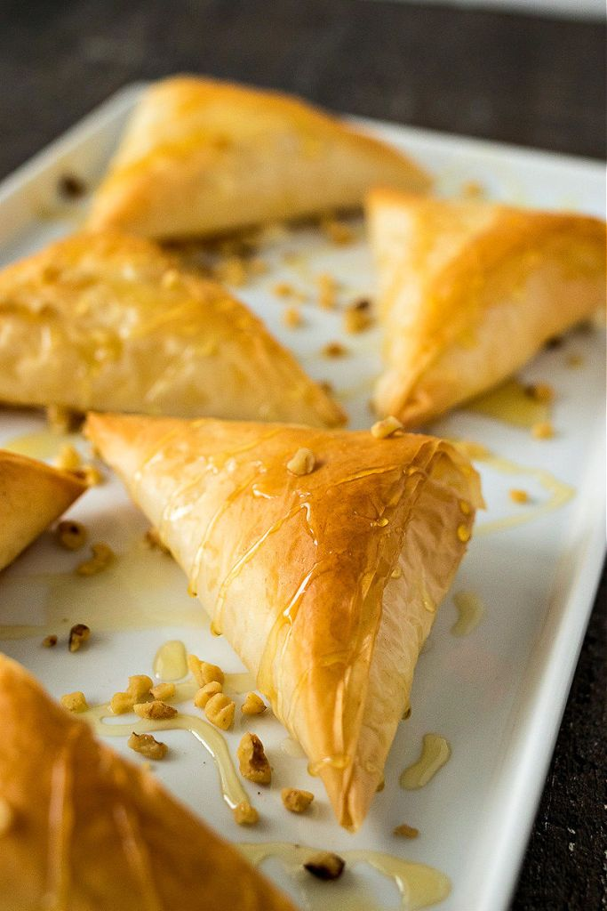 close up of a phyllo triangle sitting on a platter drizzled with honey and chopped walnuts shot from the right side