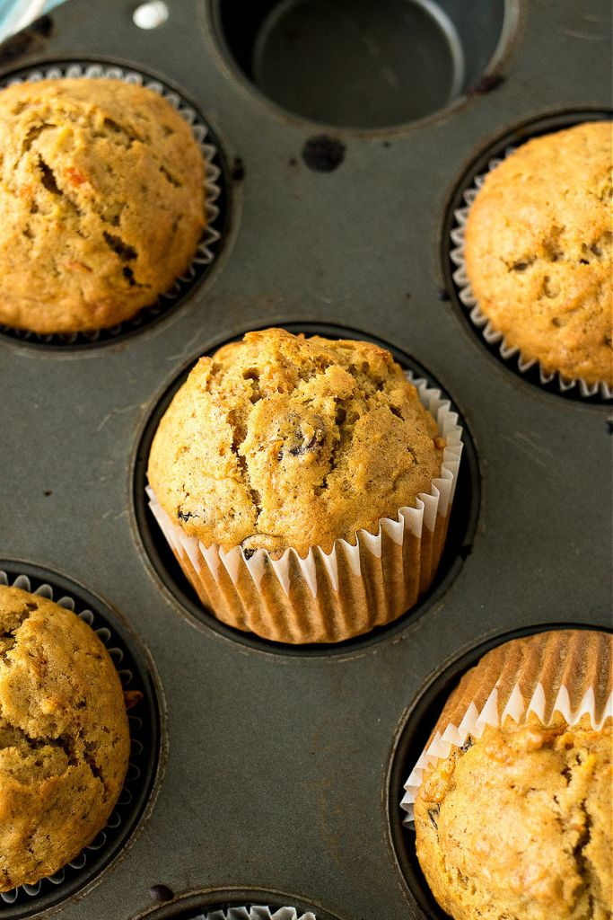zoomed in shot of baked carrot raisin muffins sitting in muffin tin at an angle