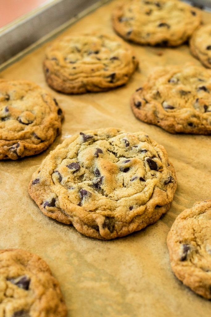 photo of chocolate chip cookie on baking sheet with more cookies in the background
