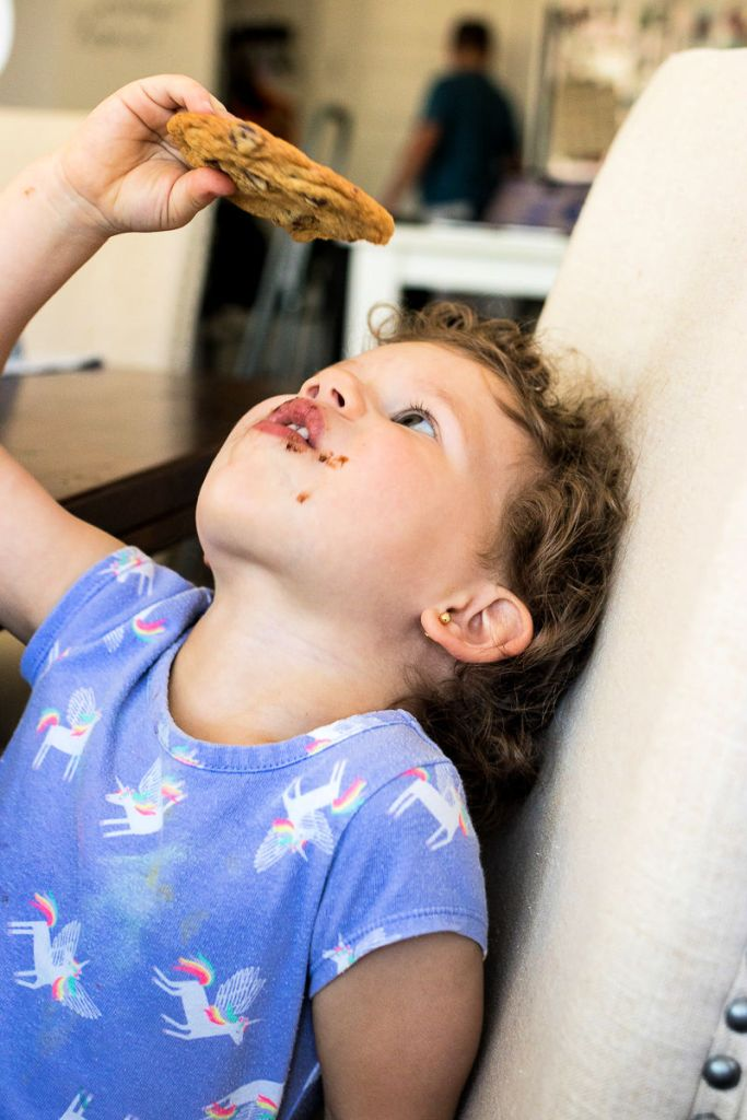 photo of young girl enjoying a chocolate chip cookie with chocolate on her face