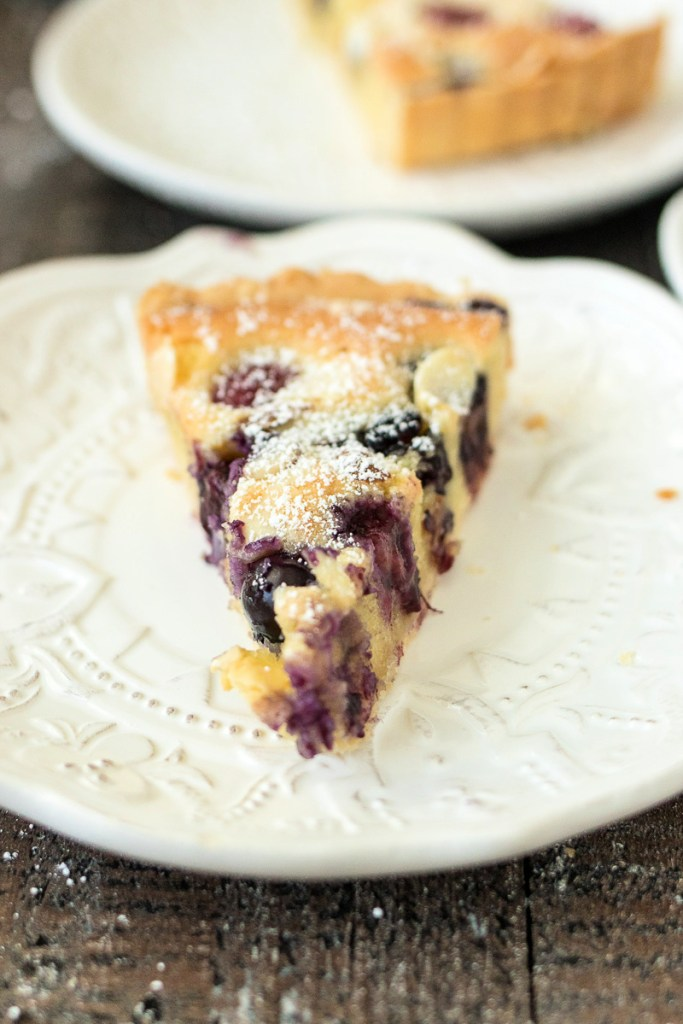 slice of mixed berry almond tart sitting on a white plate