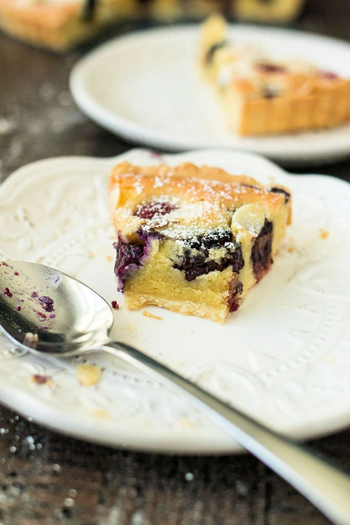 slice of mixed berry almond tart sitting on a white plate with a metal spoon with a few bites removed
