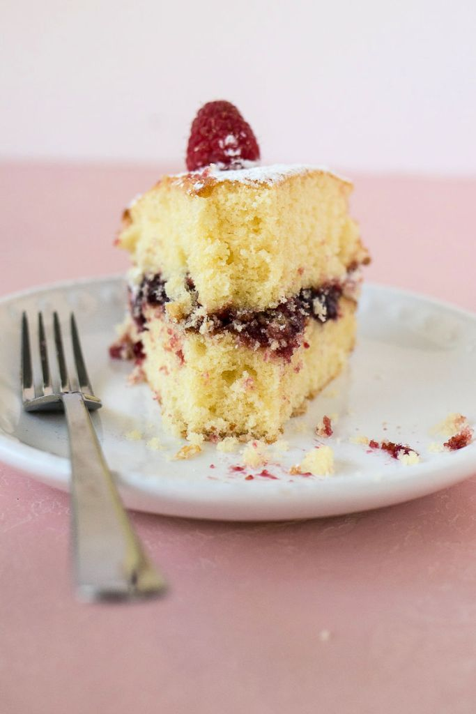 a slice of victoria sandwich cake with a bite remove and a few crumbs on the plate