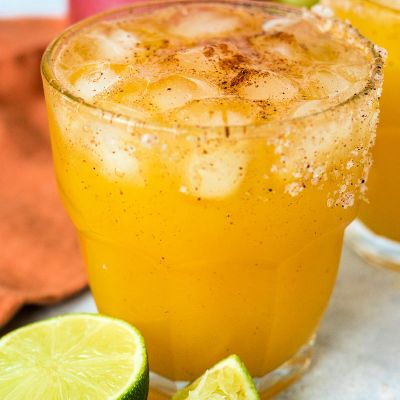 close up of chili mango margaritas with salted rim and limes in the foreground