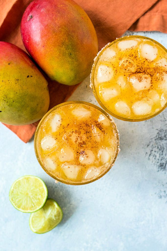overhead shot of two glasses of chili mango margaritas with limes and mangos