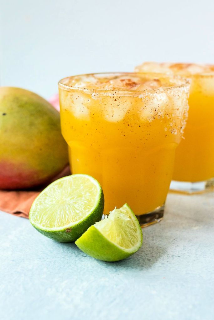 zoomed out shot of two glasses of chili mango margaritas with cut limes in the foreground and mangos in the backgroun