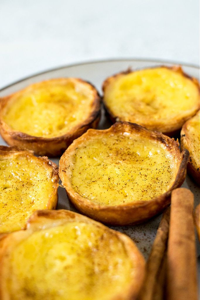 shot of portuguese egg tarts sitting on a plate with focus on the center tart