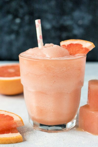 grapefruit gin slushie in a short glass with a grapefruit wedge garnish and a straw