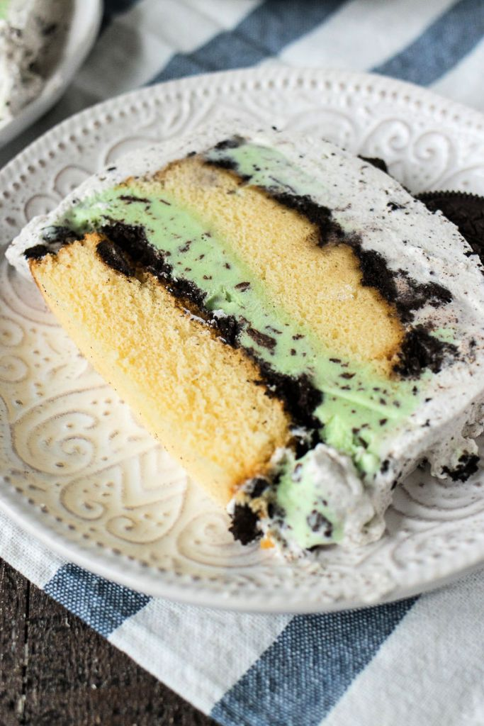 angled shot of slice of mint cookie ice cream cake sitting on a plate