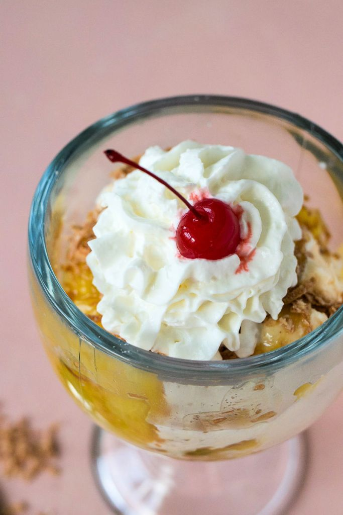 overhead shot of a large goblet filled with pina colada sundae topped with whipped cream and a cherry