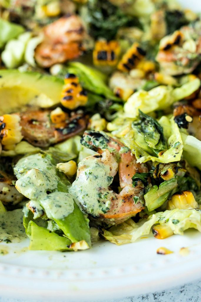 close up of grilled shrimp covered in green goddess dressing sitting on the summer salad
