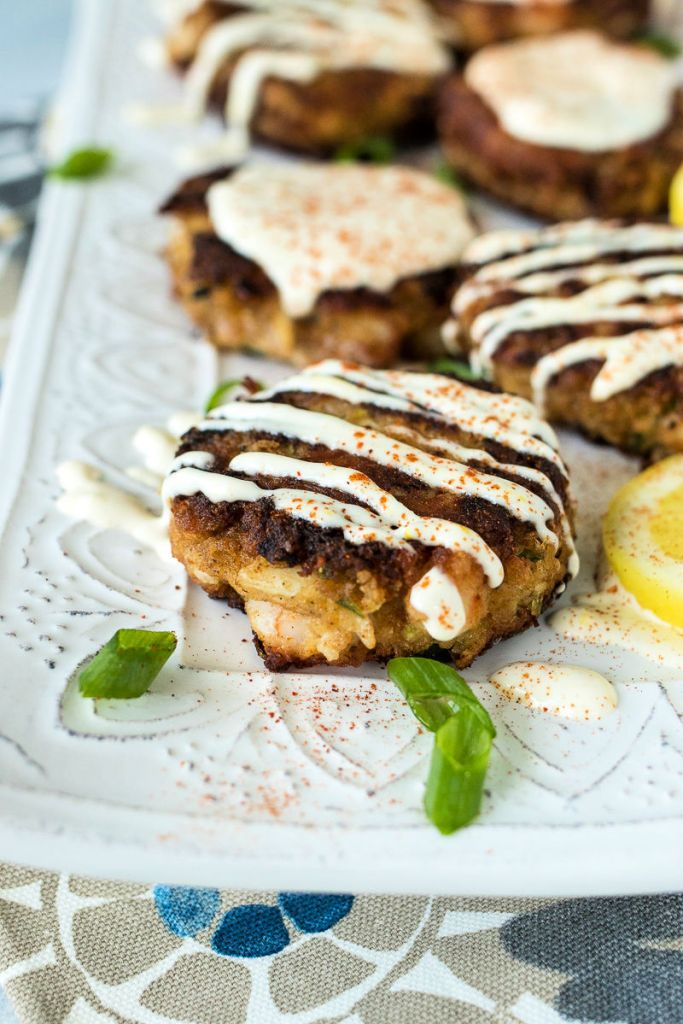 photo of shrimp crab cake on a serving platter with green onions and lemons as garnish