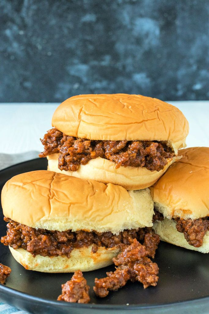 sloppy joe sitting on top of other sloppy joes on a plate