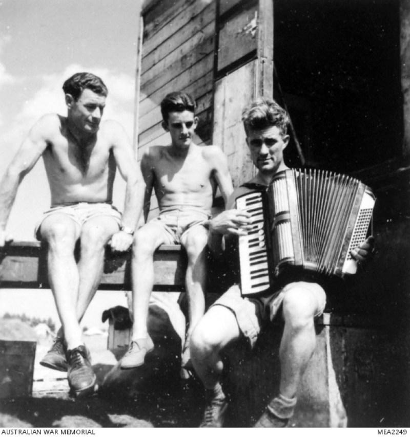 1945, l'aviere e cuoco RJ Lewis del 450° Squadron RAAF suona la fisarmonica per intrattenere J. Madigan di Melbourne pochi minuti prima del pasto serale.
