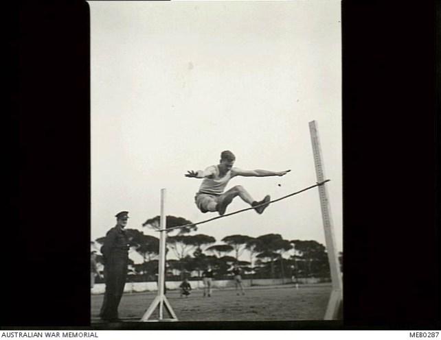 31 Marzo 1945, giornata dello sport per gli australiani del 3° Squadron RAAF. Il tempo era bello, i concorrenti erano in gran forma e gli spettatori applaudirono e urlarono a squarciagola. JB Taylor controlla la barra del salto in alto. Il campo che si vede è quello dello Stadio dei pini di Milano Marittima.