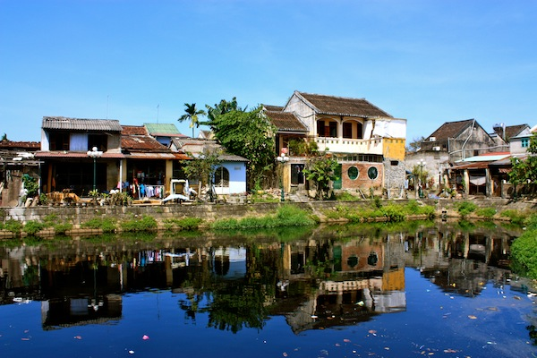 Yellow and white house reflected in water in Hoi An, Vietnam