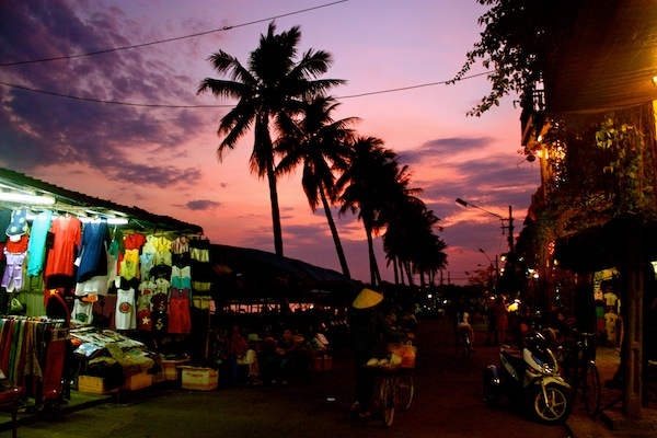 Palm trees and street stall at sunset in Hoi An, Vietnam