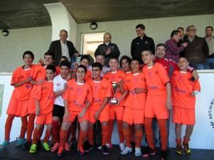 Los integrantes del Natación levantan la copa que les acredita como campeones de la Liga infantil