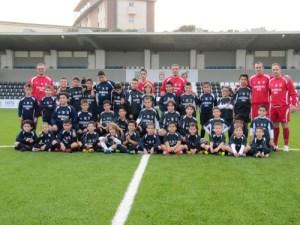Alumnos de la Escuela de Fútbol 8 posan con sus monitores en el Alfonso Murube
