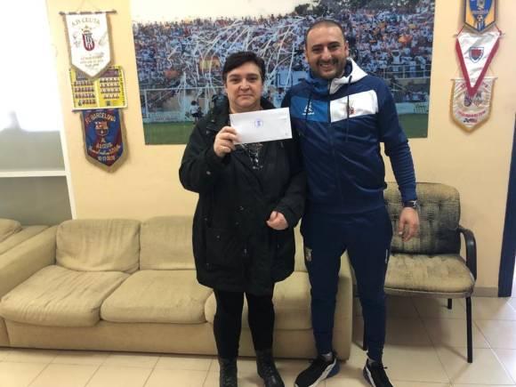 La secretaria de la AECC de Ceuta, tras recibir el sobre con la donación de manos de Luhay Hamido