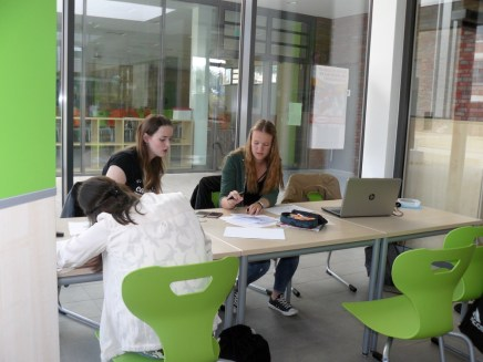 Katharina und Kristin bei einer Diskussion um Textentwürfe und Nina beim Illustrieren von Texten