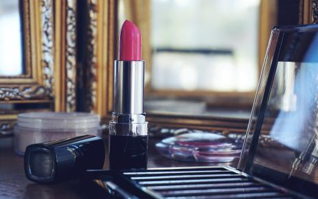 a pink lipstick in front of a mirror