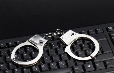 Esposas de la policía sobre el teclado de un ordenador