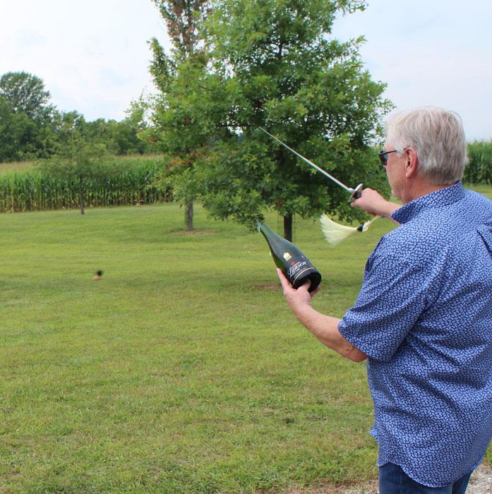 Clint Haynes sabering a Champagne bottle