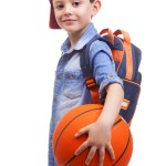 Portrait of a school kid holding a basketball, isolated on white