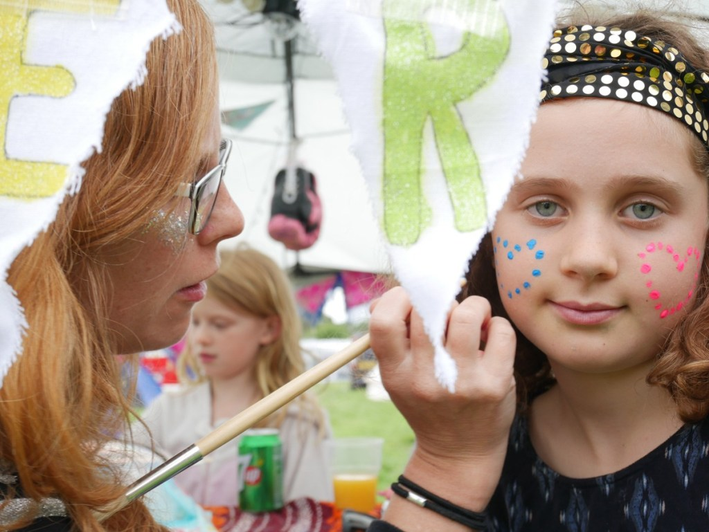 Glittery face paint, neon face decorations and more offered at DIYestival's glitter bar!