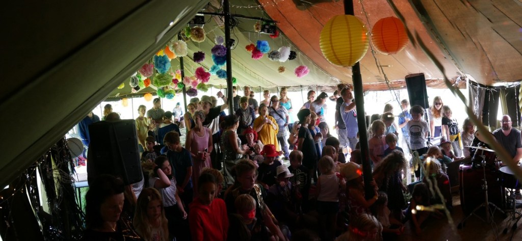 An old green army tent makes the perfect event tent with added giant paper pompoms, Chinese lanterns and fairy lights.