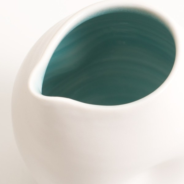 Handmade porcelain dimpled jug turquoise inside. With a matt white glaze on the outside and soft coloured inside. Available in white, grey and turquoise, in two sizes. Perfectly formed dimples to fit in your hand. Handmade by Linda Bloomfield in London. Sold on chalkandmoss.com.