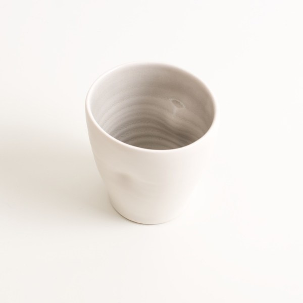 Handmade Dimpled Cup grey glaze. With a matt white glaze on the outside and soft coloured inside. Available in pale blue, pale pink, grey and turquoise. Perfectly formed dimples to fit in your hands. Hand thrown by Linda Bloomfield in her West London studio. Sold on chalkandmoss.com.