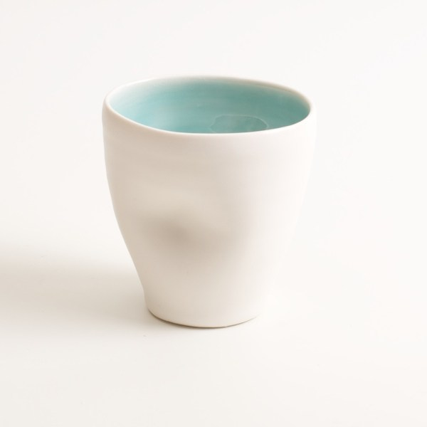 Handmade Dimpled Cup turquoise. With a matt white glaze on the outside and soft coloured inside. Available in pale blue, pale pink, grey and turquoise. Perfectly formed dimples to fit in your hand, where the shape is inspired by Japanese tea traditions. Handmade by Linda Bloomfield in London. Sold on chalkandmoss.com.
