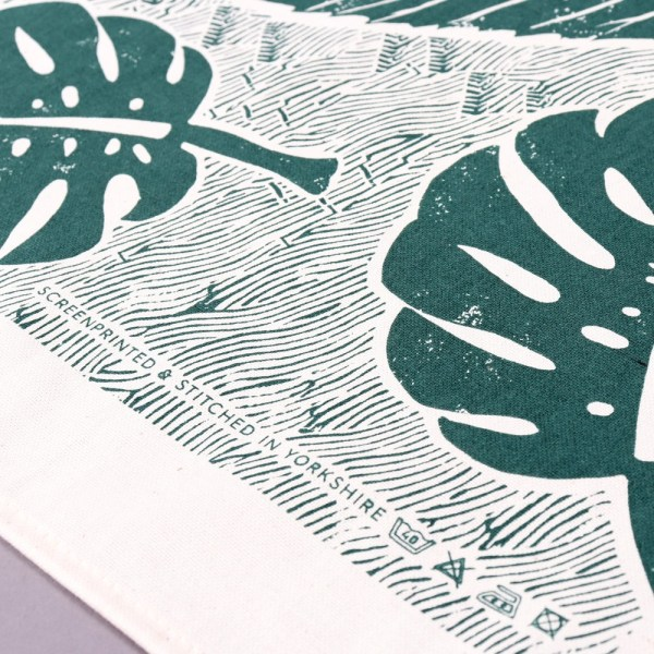 Green tea towel with a large leaf design, shown in closeup. Designed by Wald, sold on Chalk & Moss (chalkandmoss.com).