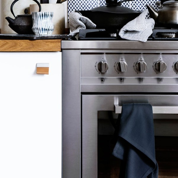 Extra large tea towel hanging on the stove, and double oven gloves on top.