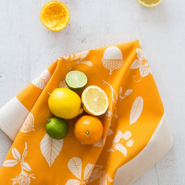 Botanical tea towel in natural, un-dyed cotton by Softer + Wild. Hand screen printed in Sussex UK. Available in many vibrant colours, seen here in orange.