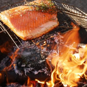 The juniper hot smoked salmon is nearly ready! See how it's crisped at the bottom of the salmon fillet and still wobbly on top? Perfect! In this recipe from Food from the Fire, you don't wait for charcoal but cook on the naked flame with juniper bushes for an extra special smoky flavour.