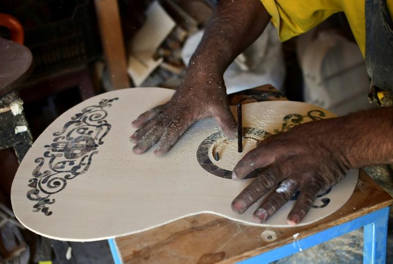 """Salvador Meza, luthier de père en fils, réalise une réplique de la guitare de Miguel, le jeune héros du film """"Coco"""", dans son atelier de Paracho, le 9 janvier 2018 au Mexique (AFP - Ronaldo SCHEMIDT)"""
