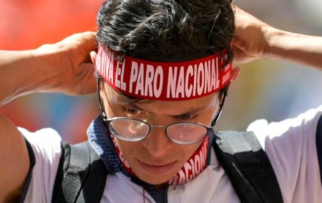 """Un étudiant attache autour du front un bandeau """"Grève nationale"""" lors de la manifestation contre la politique du président Ivan Duque, le 4 décembre à Bogota. (AFP - Raul ARBOLEDA)"""